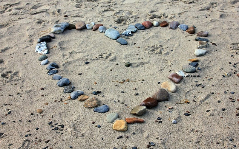 stones in heart shape on beach